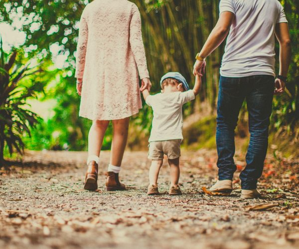 low-angle-shot-of-a-child-held-by-woman-and-man-on-on-each-3038455 (1)